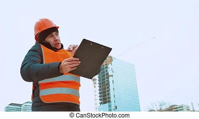 Engineering man Consulting People on construction site holding blueprint in his hand. Building inspector. Senior engineer Winter Jacket man in suit and lifestyle helmet outdoor. construction concept winter man in helmet
