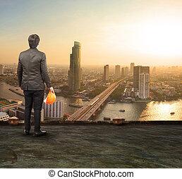 engineering man standing on top of building looking to urban sce