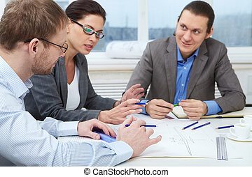 Engineering project - Three businesspeople sitting at table...