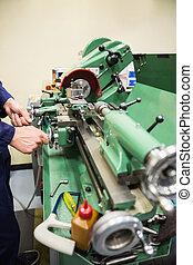 Engineering student using heavy machinery at the university