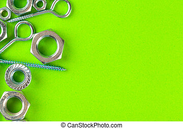 Engineering tools. Bolts and nuts on green background