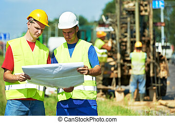 Engineers builders at road works construction site - Two ...
