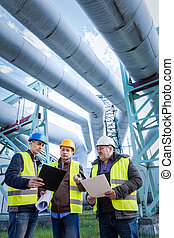 Engineers discussing maintenance of a petrochemical plant....