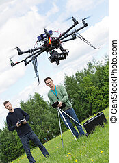 Engineers Flying UAV Drone in Park - Young engineers flying...