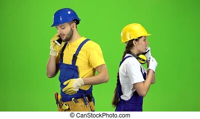 Engineers guy with a girl talking on different phones. Green screen