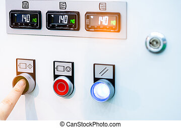 Engineer's hand push green button to open temperature control machine. Temperature control panel cabinet contain digital screen display for temperature gauge. Heat control in industrial factory.