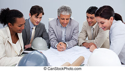 Engineers in a meeting studying plans