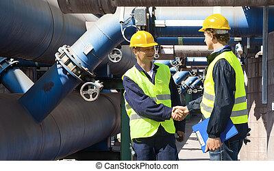 Engineers meeting - Two engineers meeting outside at the ...