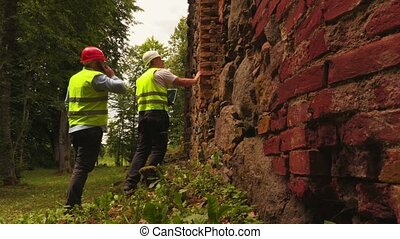 Engineers near old brick wall