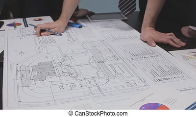 Engineers read drawing and discuss the project