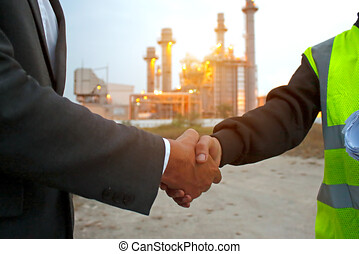 Engineers shaking hands at power plant after success day