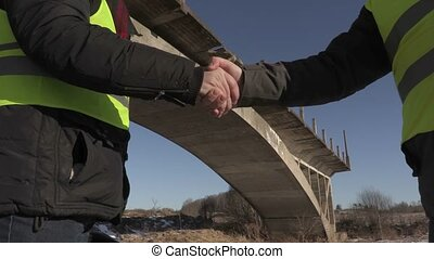 Engineers shaking hands near unfinished bridge