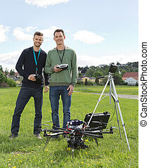 Engineers Standing By UAV Helicopter And Tripod