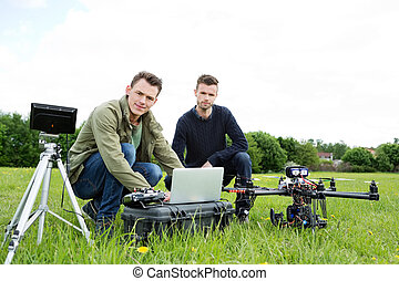 Engineers Using Laptop By UAV Helicopter