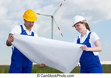 Engineers with construction plan in wind farm