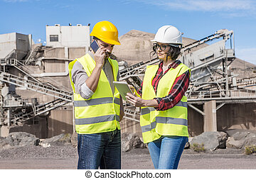 Engineers with modern gadgets working on construction site