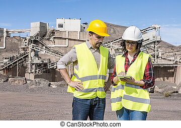 Engineers with tablet communicating on construction site