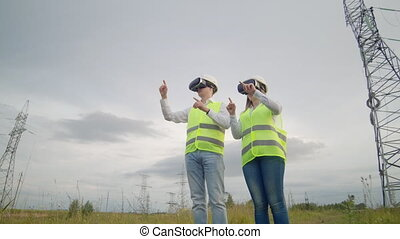 Engineers work with augmented reality using 3D virtual reality glasses. Female and male engineer works with VR glasses while a man holds.
