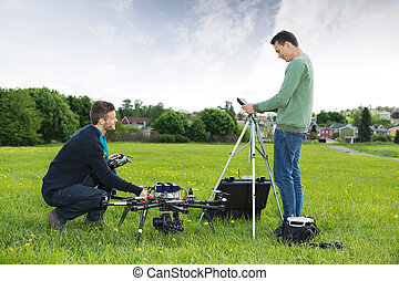 Engineers Working On UAV Helicopter in Park
