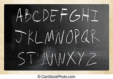 English alphabet handwritten with white chalk on a blackboard