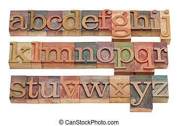 complete English alphabet (lowercase) in vintage wooden letterpress printing blocks stained by color inks, isolated on white