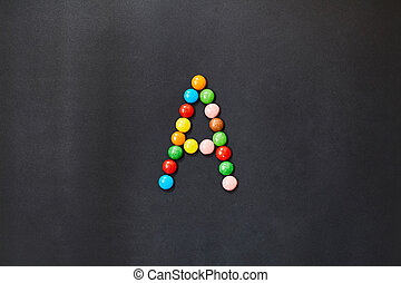 English Alphabet made of colored candies. The letter A.