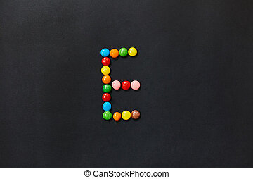 English Alphabet made of colored candies. The letter E.