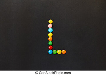 English Alphabet made of colored candies. The letter L.