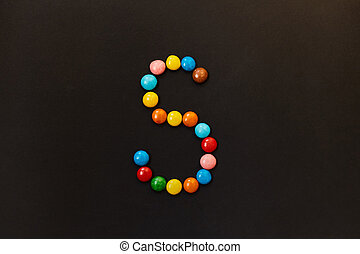 English Alphabet made of colored candies. The letter S.