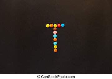 English Alphabet made of colored candies. The letter T.