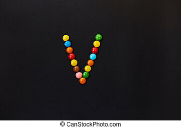 English Alphabet made of colored candies. The letter V.