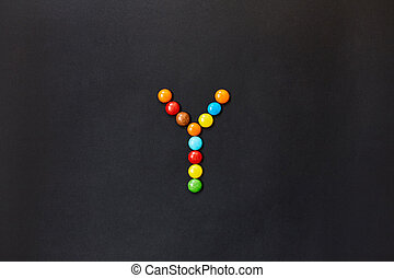 English Alphabet made of colored candies. The letter Y.