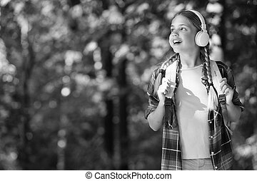English as second language. Happy child listen to headphones natural outdoors. Language learning courses. Foreign language school. New technology. Private teaching. Summer vacation, copy space.