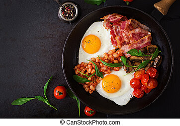 English breakfast - fried egg, beans, tomatoes, mushrooms,...