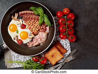 English breakfast. Fried eggs, sausages, bacon, beans, toasts, tomatoes on stone table. Top view with copy space
