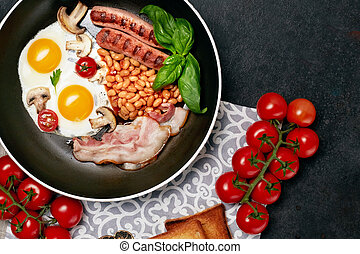 English breakfast in cooking pan with fried eggs, sausages, beans, tomatoes, mushrooms, bacon and toast on wooden background. Copy space. Top view
