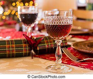 Christmas sherry in cut glass goblet on table set for Christmas lunch with crackers and decorated tree in background