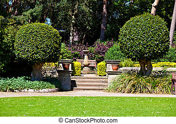 English country garden - A view of steps and a seat in an...