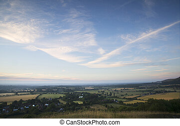 English countryside landscape during late Summer afternoon with dramatic sky and lighting