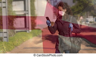 Animation of English flag waving over mixed race woman wearing face mask and using a smartphone. Covid-19 coronavirus national health safety concept digital composite