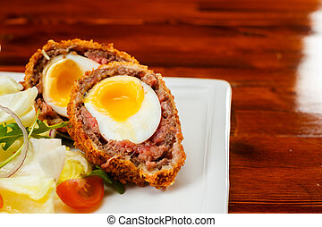 English food, Scotch eggs served with lettuce, toatoes and...