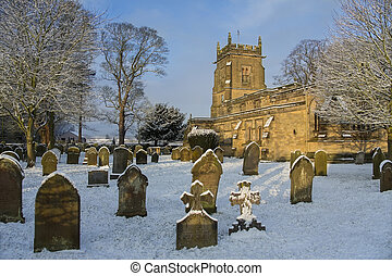 Winter snow in the graveyard of an English Parish Church in the small village of Slingsby in North Yorkshire in northern England.