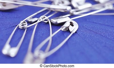 English safety pin - Weight of metal pins on a blue surface