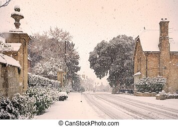 English village with snow - Cotswold high street in...