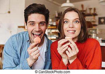 engraçado, imagem, de, bonito, par feliz, homem mulher, olhando câmera, e, comer, macaron, biscoitos