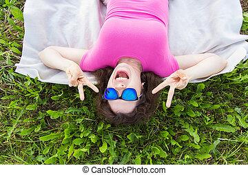 engraçado, mulher, deitando, topo, parque, jovem, retrato, capim