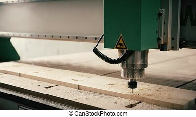 Time lapse industrial engraving machine cutting holes on lumber board on factory