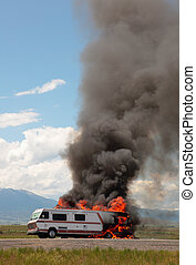 An RV is engulfed in flames at the side of a highway on a hot summer's day.