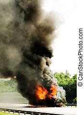 truck in fire with black smoke on the road