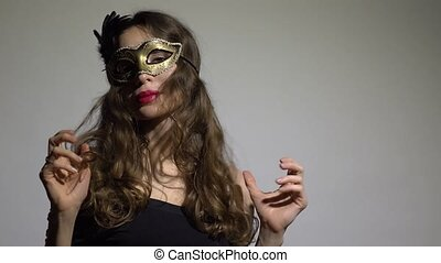 Enigmatic brunette woman wearing carnival mask poses against gray background. 4K video